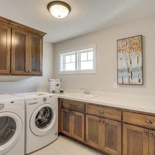 Esempio di una sala lavanderia tradizionale di medie dimensioni con lavello da incasso, ante a filo, ante in legno scuro, top in laminato, pareti grigie, pavimento in linoleum, lavatrice e asciugatrice affiancate e pavimento bianco