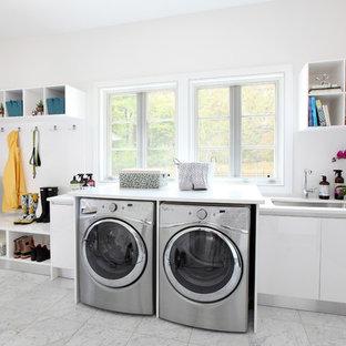 Foto på ett stort vintage linjärt grovkök, med en undermonterad diskho, släta luckor, vita skåp, vita väggar, en tvättmaskin och torktumlare bredvid varandra, bänkskiva i kvarts, marmorgolv och vitt golv