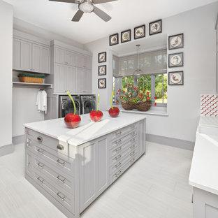 Idées déco pour une très grand buanderie classique multi-usage avec un évier encastré, un placard avec porte à panneau encastré, des portes de placard grises, un mur gris, des machines côte à côte, un sol blanc et un plan de travail blanc.