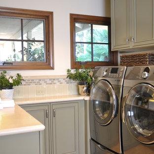 Foto på en mellanstor vintage u-formad tvättstuga, med en undermonterad diskho, luckor med infälld panel, grå skåp, bänkskiva i kalksten, vita väggar, travertin golv, en tvättmaskin och torktumlare bredvid varandra och rött golv