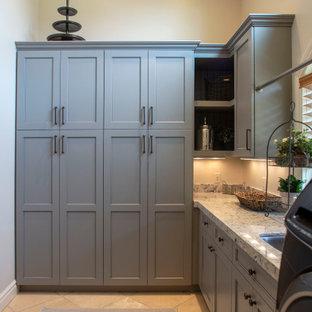 Inredning av en mellanstor flerfärgade l-formad flerfärgat tvättstuga, med en undermonterad diskho, skåp i shakerstil, grå skåp, granitbänkskiva, flerfärgad stänkskydd och en tvättmaskin och torktumlare bredvid varandra