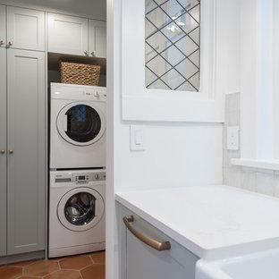 Esempio di una piccola lavanderia multiuso country con ante in stile shaker, ante verdi, pareti bianche, pavimento in terracotta, lavatrice e asciugatrice a colonna e pavimento arancione