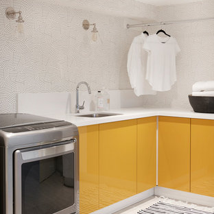 Trendy l-shaped laundry room photo in Toronto with an undermount sink, flat-panel cabinets, yellow cabinets and a side-by-side washer/dryer