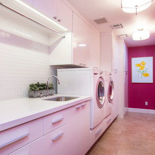 Utility room - large contemporary galley porcelain floor and beige floor utility room idea in Los Angeles with an undermount sink, flat-panel cabinets, white cabinets, quartz countertops, pink walls and a side-by-side washer/dryer