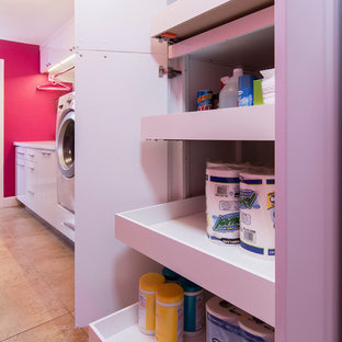 Large trendy galley porcelain floor and beige floor utility room photo in Los Angeles with an undermount sink, flat-panel cabinets, white cabinets, quartz countertops, pink walls and a side-by-side washer/dryer