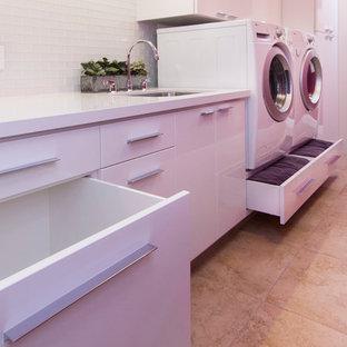 Exemple d'une grand buanderie parallèle tendance multi-usage avec un évier encastré, un placard à porte plane, des portes de placard blanches, un plan de travail en quartz modifié, un mur rose, un sol en carrelage de porcelaine et des machines côte à côte.
