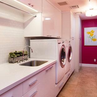 Foto di una grande lavanderia multiuso contemporanea con lavello sottopiano, ante lisce, ante bianche, top in quarzo composito, pareti rosa, pavimento in gres porcellanato e lavatrice e asciugatrice affiancate