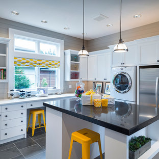 Inspiration for a traditional utility room in Portland with white cabinets, grey floors, black worktops and a stacked washer and dryer.