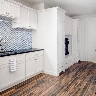 Idéer för en stor klassisk svarta linjär tvättstuga, med en enkel diskho, skåp i shakerstil, vita skåp, granitbänkskiva, grått stänkskydd, stänkskydd i stenkakel, vita väggar, klinkergolv i porslin, en tvättmaskin och torktumlare bredvid varandra och brunt golv