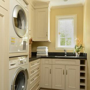 Immagine di una lavanderia classica con lavatrice e asciugatrice a colonna, ante bianche, pareti gialle e top nero