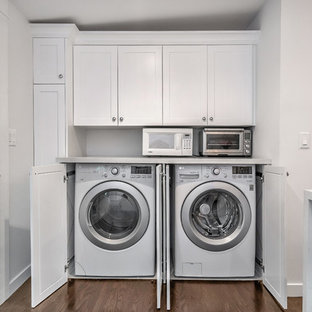 Photo of a mid-sized country u-shaped laundry room in Los Angeles with a farmhouse sink, shaker cabinets, white cabinets, quartz benchtops, white splashback, porcelain splashback, dark hardwood floors and brown floor.