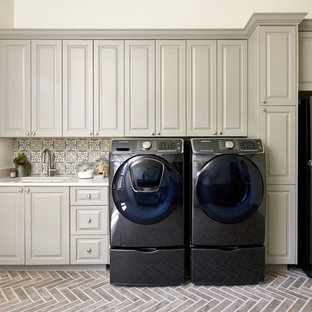 Inspiration for a huge timeless single-wall dedicated laundry room remodel in Austin with an undermount sink, raised-panel cabinets, quartz countertops, a side-by-side washer/dryer, white countertops and beige cabinets