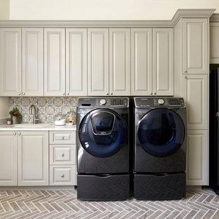 Idéer för en mycket stor klassisk vita linjär tvättstuga enbart för tvätt, med en undermonterad diskho, luckor med upphöjd panel, bänkskiva i kvarts, en tvättmaskin och torktumlare bredvid varandra och beige skåp