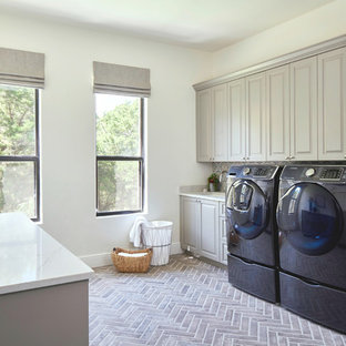 This is an example of an expansive traditional dedicated laundry room in Austin with an undermount sink, raised-panel cabinets, grey cabinets, quartz benchtops, a side-by-side washer and dryer and white benchtop.