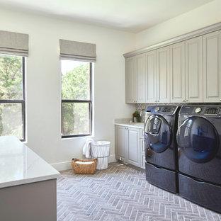 Bild på en mycket stor vintage vita vitt tvättstuga enbart för tvätt, med en undermonterad diskho, luckor med upphöjd panel, grå skåp, bänkskiva i kvarts och en tvättmaskin och torktumlare bredvid varandra
