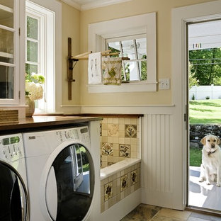 Laundry room - traditional laundry room idea in Burlington with a side-by-side washer/dryer, brown countertops and beige walls