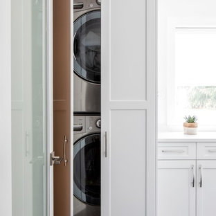Inspiration for a mid-sized contemporary single-wall black floor and marble floor dedicated laundry room remodel in Vancouver with white cabinets, white walls, a stacked washer/dryer, white countertops, recessed-panel cabinets and quartz countertops