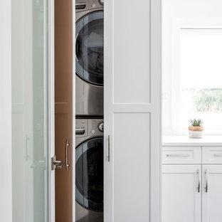 Inredning av en modern mellanstor vita linjär vitt tvättstuga enbart för tvätt, med vita skåp, vita väggar, en tvättpelare, svart golv, luckor med infälld panel, bänkskiva i kvarts och marmorgolv