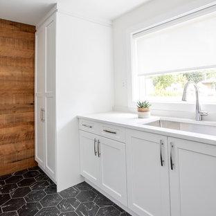 Bild på en mellanstor funkis vita linjär vitt tvättstuga enbart för tvätt, med en undermonterad diskho, luckor med infälld panel, vita skåp, bänkskiva i kvarts, vita väggar, marmorgolv, en tvättpelare och svart golv