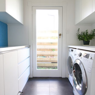 Inspiration for a mid-sized modern galley dedicated laundry room in Auckland with flat-panel cabinets, white cabinets, stainless steel benchtops, blue splashback, glass tile splashback, a side-by-side washer and dryer and white benchtop.