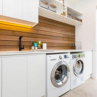 Idéer för att renovera en funkis vita linjär vitt tvättstuga, med en undermonterad diskho, släta luckor, vita skåp, betonggolv, en tvättmaskin och torktumlare bredvid varandra och grått golv