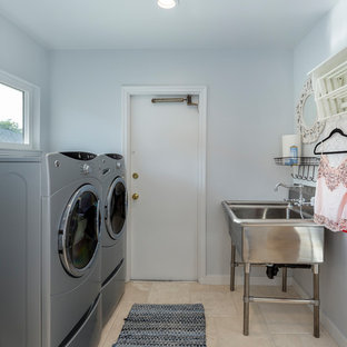 Exemple d'une petit buanderie chic en U dédiée avec un évier utilitaire, un mur blanc, des machines côte à côte, des portes de placard blanches, un sol en travertin et un placard avec porte à panneau encastré.