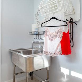 Idéer för små vintage tvättstugor enbart för tvätt, med en allbänk, vita väggar, en tvättmaskin och torktumlare bredvid varandra, vita skåp, travertin golv och luckor med infälld panel