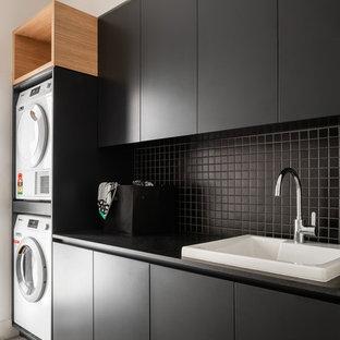 Foto på ett funkis svart linjärt grovkök, med en nedsänkt diskho, släta luckor, svarta skåp och en tvättpelare