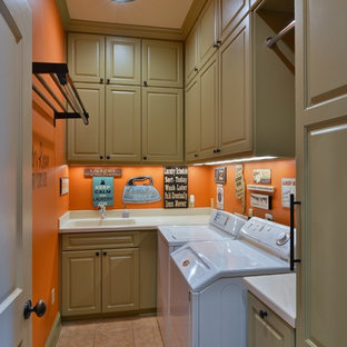 Inspiration for a mid-sized timeless l-shaped ceramic tile dedicated laundry room remodel in Houston with an integrated sink, raised-panel cabinets, green cabinets, solid surface countertops, orange walls and a side-by-side washer/dryer
