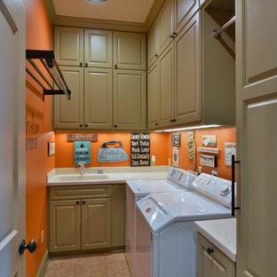 Idee per una sala lavanderia chic di medie dimensioni con lavello integrato, ante con bugna sagomata, ante verdi, top in superficie solida, pareti arancioni, pavimento con piastrelle in ceramica e lavatrice e asciugatrice affiancate