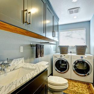 Foto di una piccola lavanderia multiuso design con lavello sottopiano, ante in stile shaker, ante verdi, lavatrice e asciugatrice affiancate, pavimento marrone, top bianco e pareti grigie