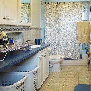 Cette photo montre une buanderie chic en U multi-usage et de taille moyenne avec un évier intégré, un placard à porte plane, des portes de placard blanches, un plan de travail en stratifié, un mur blanc, un sol en vinyl et des machines superposées.