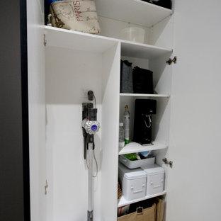 Bild på en mellanstor vintage vita parallell vitt tvättstuga enbart för tvätt, med en undermonterad diskho, skåp i shakerstil, svarta skåp, bänkskiva i kvarts, vitt stänkskydd, stänkskydd i tunnelbanekakel, grå väggar, ljust trägolv, en tvättmaskin och torktumlare bredvid varandra och brunt golv