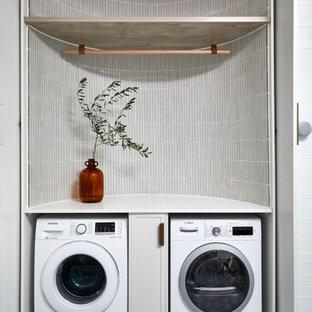Maritim inredning av en mellanstor tvättstuga, med skåp i mellenmörkt trä, vita väggar och blått golv