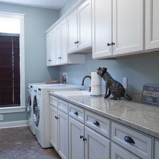 Inspiration för en stor vintage flerfärgade linjär flerfärgat tvättstuga enbart för tvätt, med en nedsänkt diskho, luckor med infälld panel, vita skåp, granitbänkskiva, blå väggar, klinkergolv i porslin, en tvättmaskin och torktumlare bredvid varandra och flerfärgat golv