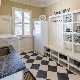 Exempel på ett mellanstort klassiskt parallellt grovkök, med en undermonterad diskho, öppna hyllor, vita skåp, bänkskiva i täljsten, beige väggar, klinkergolv i porslin och en tvättmaskin och torktumlare bredvid varandra
