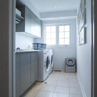 Ispirazione per una piccola sala lavanderia nordica con lavello da incasso, ante lisce, ante grigie, top in laminato, pareti bianche, pavimento in gres porcellanato, lavatrice e asciugatrice affiancate, pavimento grigio e top grigio