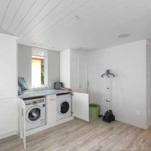 Inspiration for a small beach style single-wall laundry cupboard in Other with shaker cabinets, white cabinets, quartzite benchtops, white walls, vinyl floors, a concealed washer and dryer, grey floor, white benchtop and timber.