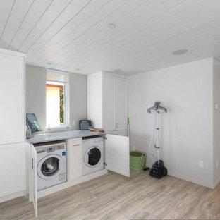 Cette photo montre une petit buanderie linéaire bord de mer avec un placard, un placard à porte shaker, des portes de placard blanches, un plan de travail en quartz, un mur blanc, un sol en vinyl, des machines dissimulées, un sol gris, un plan de travail blanc et un plafond en lambris de bois.