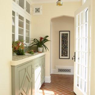 Idee per una lavanderia multiuso tradizionale con lavello sottopiano, ante con riquadro incassato, ante verdi, top piastrellato, pavimento in terracotta, lavatrice e asciugatrice nascoste e pareti beige