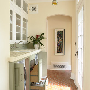 Elegant single-wall terra-cotta floor utility room photo in Minneapolis with an undermount sink, recessed-panel cabinets, green cabinets, tile countertops, a concealed washer/dryer and beige walls