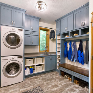 Inspiration for a timeless l-shaped gray floor utility room remodel in Minneapolis with an undermount sink, shaker cabinets, blue cabinets, white walls, a stacked washer/dryer and gray countertops