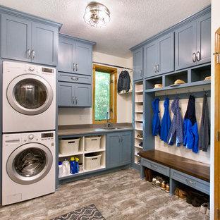 Foto di una lavanderia multiuso tradizionale con lavello sottopiano, ante in stile shaker, ante blu, pareti bianche, lavatrice e asciugatrice a colonna, pavimento grigio e top grigio