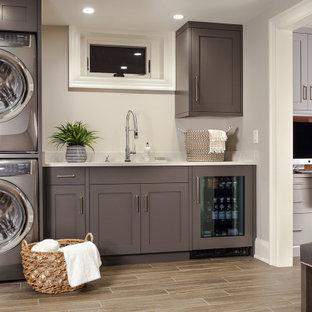 Idee per una lavanderia multiuso classica di medie dimensioni con lavello sottopiano, ante lisce, ante grigie, top in quarzo composito, pareti grigie, pavimento con piastrelle in ceramica, lavatrice e asciugatrice a colonna, pavimento marrone e top bianco