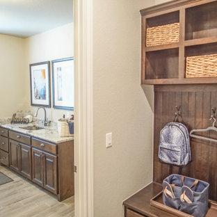 Inredning av ett klassiskt mellanstort flerfärgad parallellt flerfärgat grovkök, med en undermonterad diskho, öppna hyllor, bruna skåp, granitbänkskiva, grå väggar, klinkergolv i keramik, en tvättmaskin och torktumlare bredvid varandra och grått golv