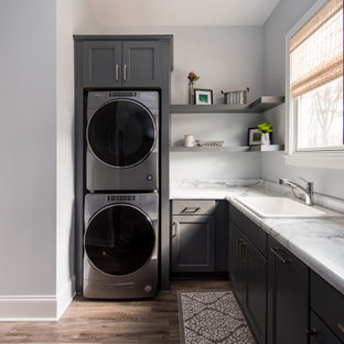 Mid-sized transitional l-shaped dark wood floor dedicated laundry room photo in Indianapolis with an undermount sink, shaker cabinets, gray cabinets, marble countertops, beige walls and a stacked washer/dryer