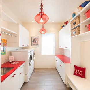 Design ideas for a large contemporary galley utility room in Albuquerque with a submerged sink, flat-panel cabinets, white cabinets, beige walls, porcelain flooring, a side by side washer and dryer, brown floors and red worktops.