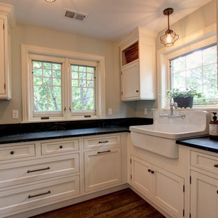 Foto di una grande sala lavanderia country con lavatoio, ante bianche, top in saponaria, pareti beige, parquet scuro, lavatrice e asciugatrice affiancate e ante a filo