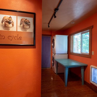 Cette photo montre une buanderie linéaire sud-ouest américain dédiée et de taille moyenne avec un mur orange, un sol en bois brun, des machines superposées et un sol marron.