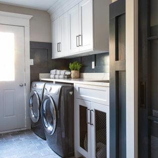 Foto på en vintage vita parallell tvättstuga, med en undermonterad diskho, luckor med infälld panel, vita skåp, bänkskiva i kvarts, vitt stänkskydd, blå väggar, klinkergolv i porslin, en tvättmaskin och torktumlare bredvid varandra och grått golv